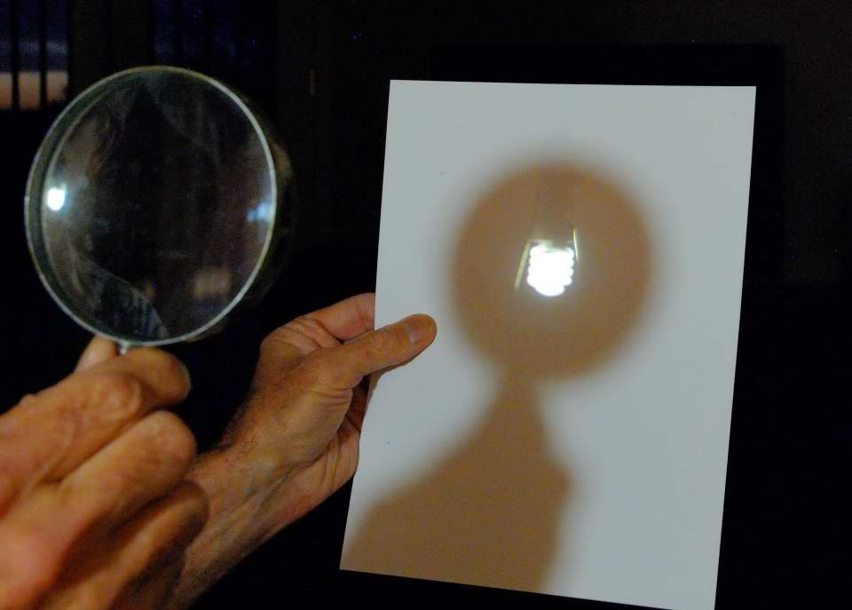 Light bulb projected onto paper with a magnifying glass. MAS image by Gene Hanson.